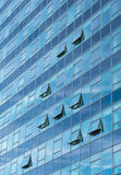Architectural detail of a modern glass skyscraper building. Architectural detail of a modern blue glass skyscraper building with open windows stock photography