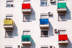 Architectural detail and pattern of modern residential building with colorful balconies and windows of apartments. royalty free stock photos