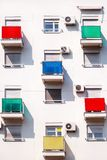 Architectural detail and pattern of modern residential building with colorful balconies and windows of apartments. royalty free stock photography