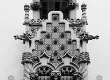 Architectural detail with perfect symmetry. Shot in black and white detail on the sculpture on the facade of this historic building representing some characters Stock Images