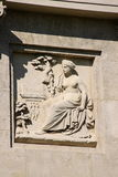Architectural detail of the sculpture of lady sitting by the tree Royalty Free Stock Photos