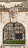 Architectural detail: stone wall with iron glille and mask Royalty Free Stock Photography
