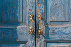 Architectural detail of a vintage brass door handle. Vintage antique door handle on the old blue wooden door Royalty Free Stock Photo