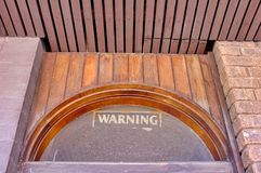 Architectural Detail, Warning Notice on Old Glass Windoe. Architectural detail of a run down old building, with a warning sign on a high set half round glass stock photo