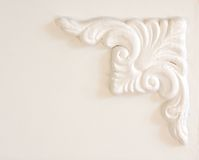 Architectural details. Carved white mouldings on a white, wooden wall; in vertical orientation Royalty Free Stock Photography