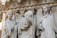 Architectural details of Cathedral Notre Dame de Paris on Cite island in Paris Saint Denis holding his head. France Stock Photography