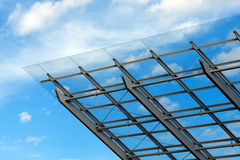 Architectural Details of a Glass and Steel Building. Detail of steel and glass roof of a modern building with blue sky and clouds stock photo