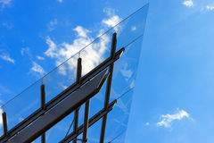 Architectural Details of a Glass and Steel Building. Detail of steel and glass roof of a modern building with blue sky and clouds stock photos