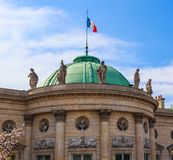 Architectural details of a historic building facade with a french flag on the roof. Paris, France. April 2019.  royalty free stock photography