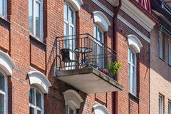 Architectural details of modern apartment building. Balcony with chairs and flowers. Architectural details of modern apartment building. Balcony with chairs and royalty free stock photography