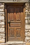 Architectural details of a weathered doors on an old stone house in a narrow winding streets at the old town of Skiathos. Island of Skiathos, Greece stock image