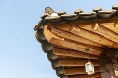 Architectural details of wooden eaves and ceramic tile roof ends of tradition house at Korean ancient village in South Korea. Architectural details of wooden stock photography