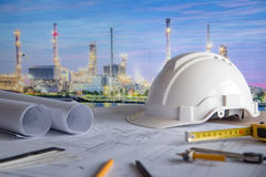 Architectural drawing and project tools on work table. Architectural drawing plan of refinery plant with blueprint rolls, protection safety helmet and project stock photo