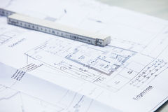 Architectural drawings and ruler. Architectural drawings showing details and dimensions of the floorplan of a residential house with a builders ruler laid on top Royalty Free Stock Photo