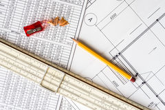 Architectural drawings, slide rule and a sharpener with a pencil Stock Photos