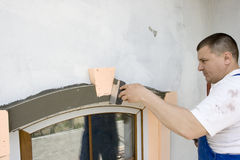 Architectural element. Plasterer inflicts mortar on architectural element Stock Image