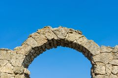 Stone arch against a blue sky. Architectural element. Fragment of an old stone arch against a blue sky Royalty Free Stock Image