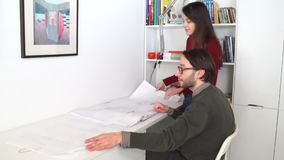 Architectural engineers work with blueprints and discussing building model design for the urban plnning proj. Young male and female architectural engineers work stock video footage