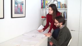 Architectural engineers work with blueprints and discussing building model design for the urban plnning proj. Young male and female architectural engineers work stock video