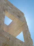 Architectural geometry. Modern architectural composition of rough marble intersecting walls and a clear, sunny sky Stock Images