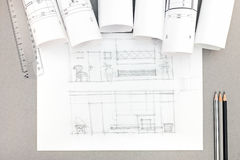 Architectural hand-drawn sketch with blueprint rolls on desktop Stock Photos