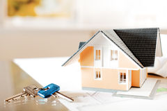Architectural Miniature Home on Blueprint with Key Stock Photo