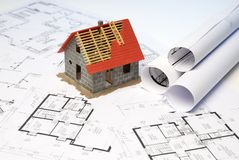 Architectural model of a building shell on blueprints. Architectural model of a building shell stands on blueprints stock images