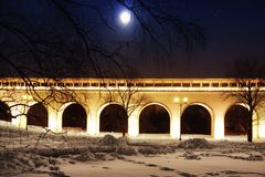 Architectural monument. Beautiful aqueduct bridge in winter against the background of the starry sky with the moon.  Royalty Free Stock Photos