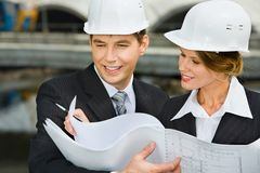 Architectural plan. Confident female worker is showing a architectural plan to her chief stock photography