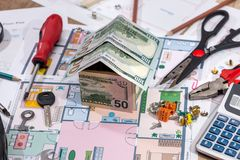 Architectural plan house with money pencil calculator and work tools royalty free stock photos