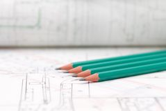 Architectural plans lying on drawing board. With green pencils royalty free stock images