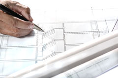 Architectural plans project drawing and blueprints rolls with eq. Engineer hand holding pen point to architectural plans project drawing, architect engineering Stock Image