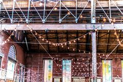 Architectural Post and Beam. An old warehouse with open ceiling, exposing the structural support. Brick, wood and steel/iron. Strings of lights are also shown Stock Photos