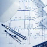 Architectural project, blueprints, blueprint rolls, compass divider, calculator, white safety on plans. Engineering tools view fro Royalty Free Stock Photography