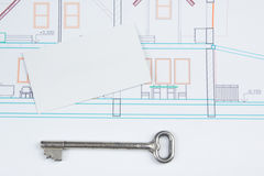 Architectural project, blueprints, key with house figure and blank business card on wooden background. Real Estate Stock Photography