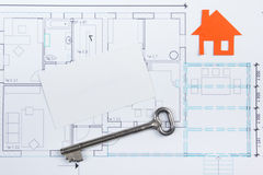Architectural project, blueprints, key with house figure and blank business card on wooden background. Real Estate Stock Photos