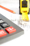 Architectural project and calculator. Architectural project, calculator and ruler close up, vertical, copy space. Cost of construction concept stock photography