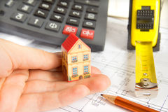 Architectural project. Little model of house in female hand, calculator and ruler close up. Cost and plan of construction concept royalty free stock photo