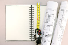 Architectural project with notepad and tape measure on desk Royalty Free Stock Photography