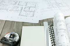 Architectural project with notepad and tools on gray wooden desk Stock Images