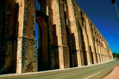 Architectural structure of the aqueduct with arches on the road to Elvas. Architectural structure of the Amoreira Aqueduct with arches and pillars on the road to royalty free stock photography