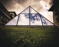 Architectural structure in the shape of a pyramid and built with transparent glass. Architecture of houses and buildings in the European Alps, modern and stock photography
