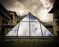 Architectural structure in the shape of a pyramid and built with transparent glass. Architecture of houses and buildings in the European Alps, modern and stock image
