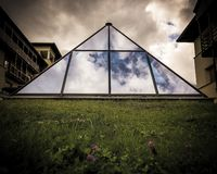 Architectural structure in the shape of a pyramid and built with transparent glass. Architecture of houses and buildings in the European Alps, modern and stock photos