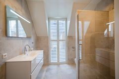 Architecturally built bathroom with luxury tiling, white shutters, bath and spacious rain shower stock image