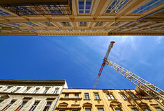 Architecture. Crane between parallel buildings, against the blue sky Royalty Free Stock Photos