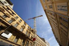 Architecture. Crane between buildings, against the blue sky Royalty Free Stock Photo