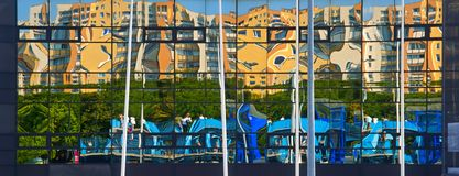 Architecture, abstract, reflection residential blocks in the glass facade, urban scene Stock Photos