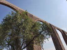Ancient aqueduct of arches on a street in Queretaro, Mexico. Architecture and ancient construction, city with tradition and history of Mexico, travel and tourism royalty free stock images