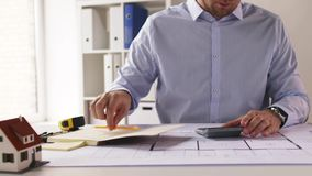 Architect with blueprint counting on calculator stock footage